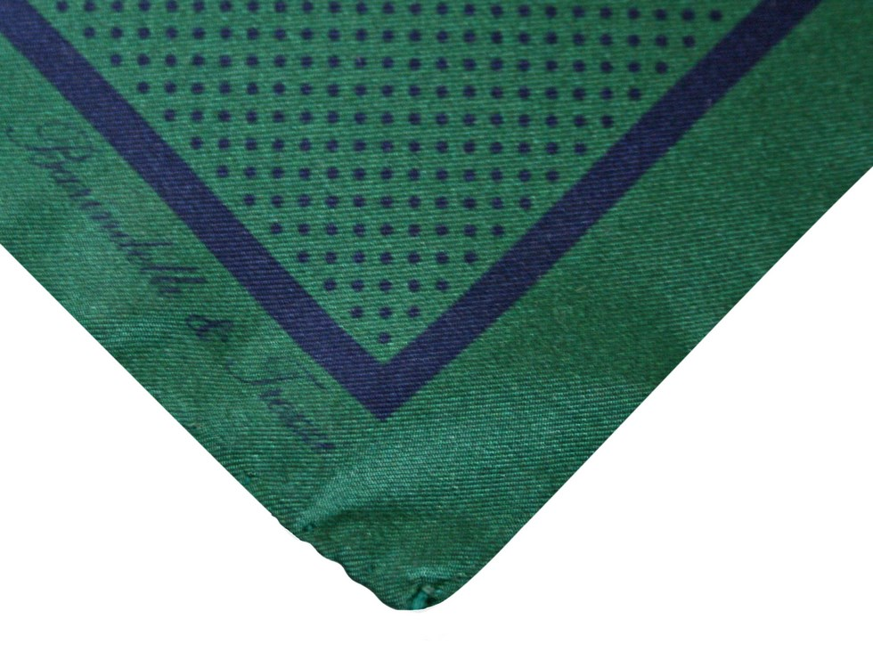 Classic silk handkerchief with blue polka dot pattern on a green